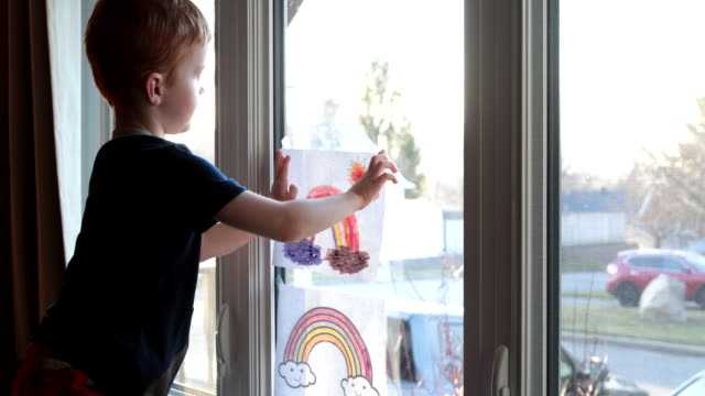 young boy sticking his rainbow drawing on home window during the covid-19 crisis at sunset - waving hands stock videos & royalty-free footage