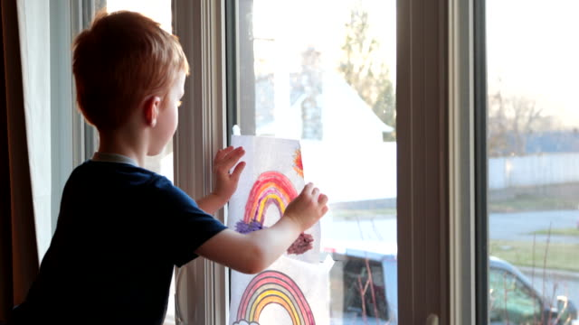young boy sticking his rainbow drawing on home window during the covid-19 crisis at sunset - arcobaleno video stock e b–roll