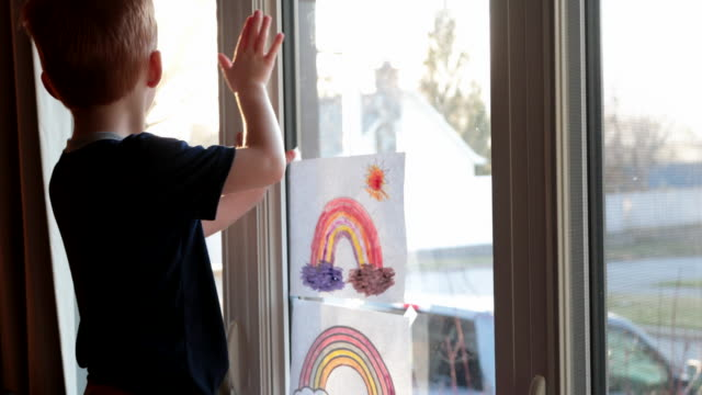 young boy sticking his rainbow drawing on home window during the covid-19 crisis at sunset - window stock videos & royalty-free footage