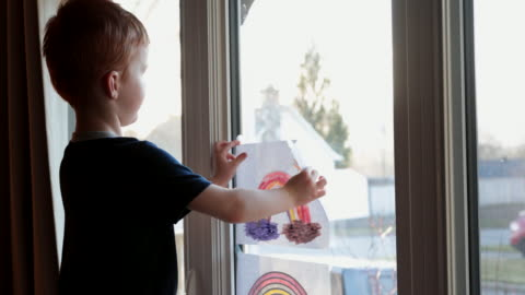 young boy sticking his rainbow drawing on home window during the covid-19 crisis at sunset - rainbow stock videos & royalty-free footage