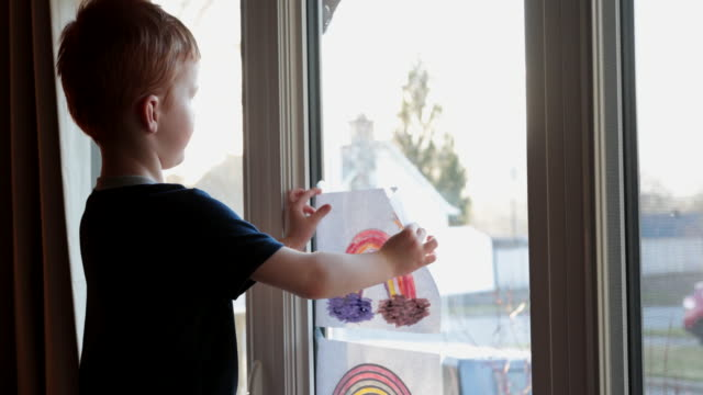 young boy sticking his rainbow drawing on home window during the covid-19 crisis at sunset - child stock videos & royalty-free footage