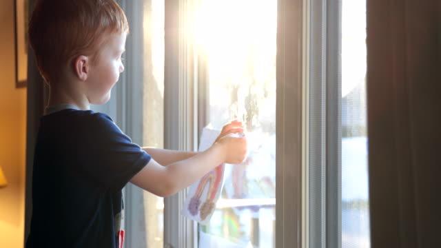vídeos y material grabado en eventos de stock de young boy metiendo su arco iris dibujando en la ventana de casa durante la crisis de covid-19 al atardecer - dibujar