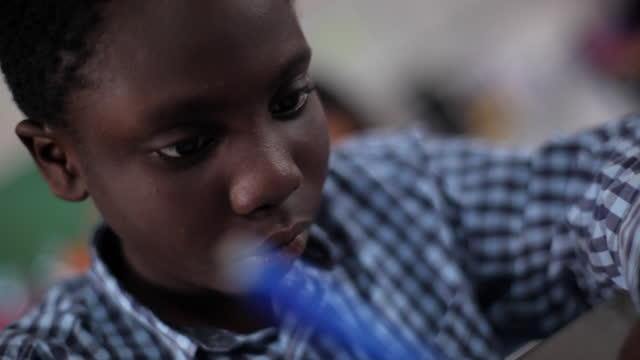 vídeos de stock, filmes e b-roll de a young boy struggles to stay awake while completing an assignment in class. - frustração