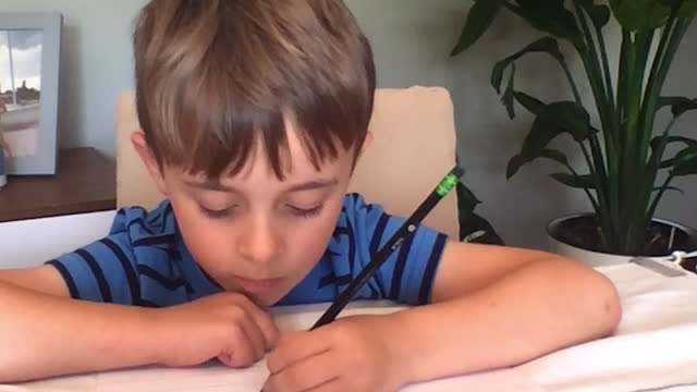 cu of young boy studying quietly during an online class session - one boy only stock videos & royalty-free footage