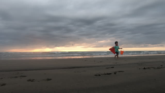 young boy superhero playing on murawai beach new zealand at sunset - boys stock videos & royalty-free footage