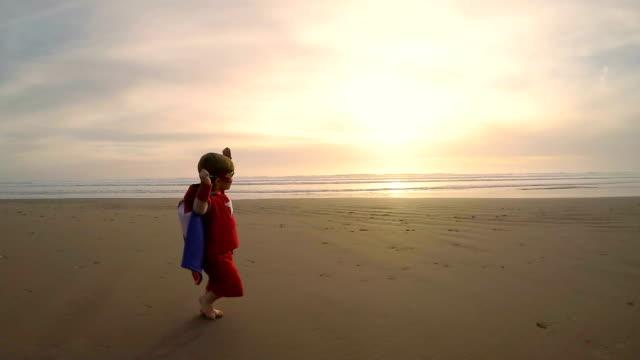 stockvideo's en b-roll-footage met jonge jongen superheld uitgevoerd op california beach - 2 3 jaar