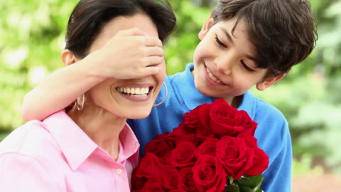 ms pan young boy surprising mother with bouquet of red roses / richmond, virginia, usa - mother's day stock videos & royalty-free footage