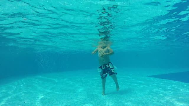 Young boy swimming underwater in a pool