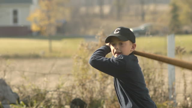 ms slo mo young boy swinging and hiting baseball / chelsea, michigan, united states - swinging stock videos & royalty-free footage