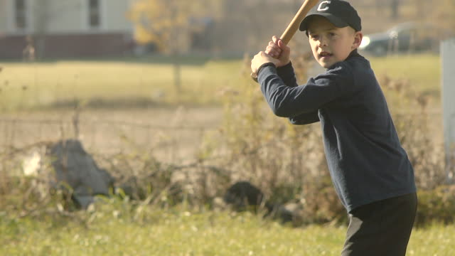 MS SLO MO Young boy swinging and hiting baseball / Chelsea, Michigan, United States