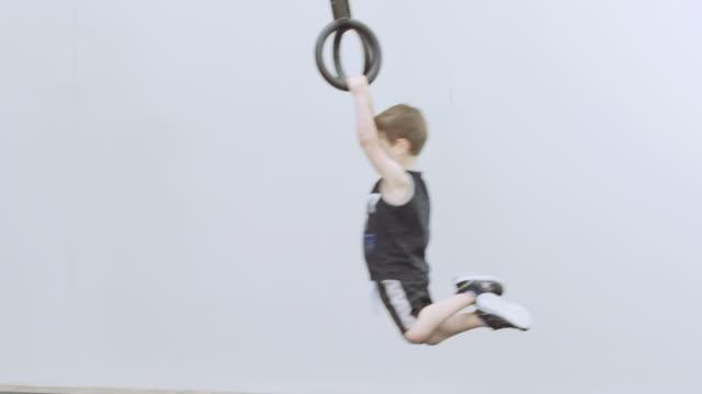 Ung pojke svängande på ringar i en crosstraining klass för barn