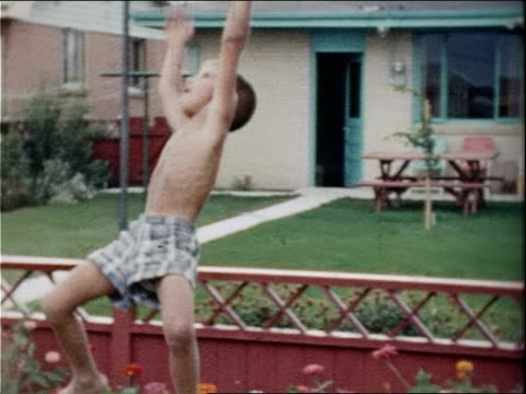 a young boy swings from monkey bars in a back yard. - anno 1958 video stock e b–roll