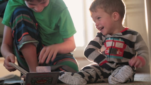 stockvideo's en b-roll-footage met young boy takes a break from doing homework to read a book to toddler boy while celebrating thanksgiving morning with family - pyjama