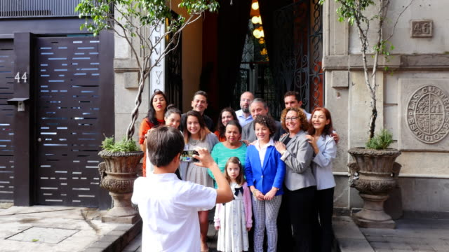 ms tu td young boy taking digital photo with smartphone of smiling multigenerational family in front of restaurant entrance - photo messaging stock videos & royalty-free footage