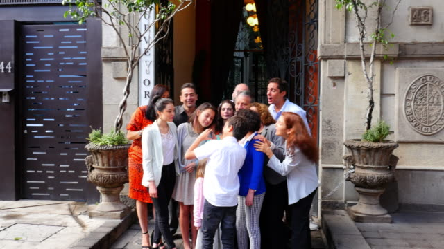 ms swish pan young boy taking multigenerational family portrait with smartphone and showing it to smiling family in front of restaurant entrance - kleid stock-videos und b-roll-filmmaterial