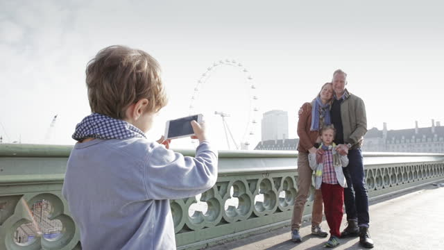 vidéos et rushes de young boy taking photo of family during a trip to london - capitales internationales