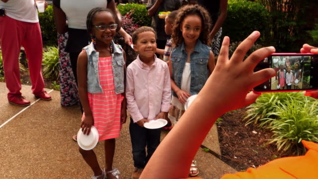 ms young boy taking photos of cousins with smartphone during family celebration - young family stock videos & royalty-free footage