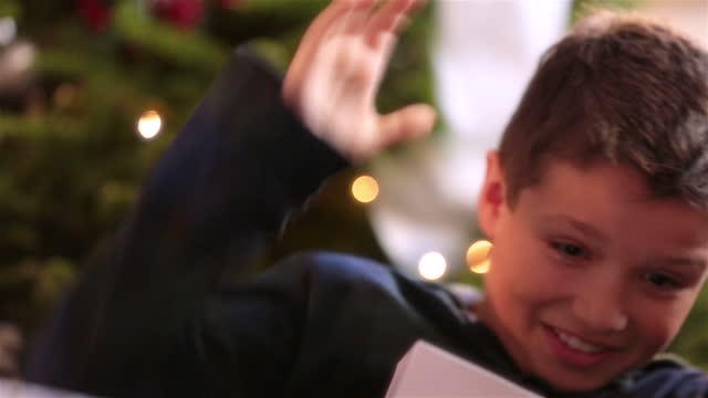 young boy tears off wrapping paper in a frenzy in front of christmas tree - christmas wrapping paper stock videos & royalty-free footage