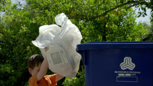 a young boy throws a bag of plastic bottles into a recycling bin. - bin bag stock videos & royalty-free footage