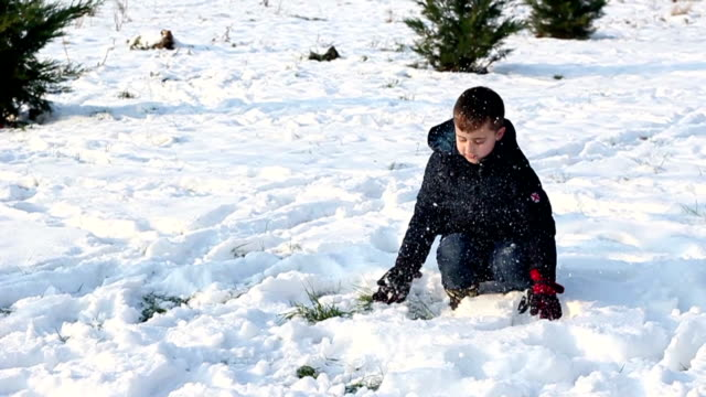 Young boy throws snow into air, slow motion