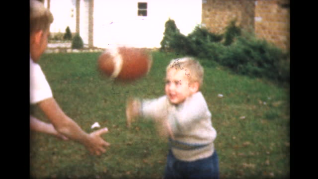 1957 young boy tries to toss football - di archivio video stock e b–roll