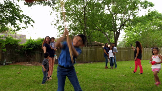 ms young boy trying to break open pinata during birthday party - papier stock videos & royalty-free footage