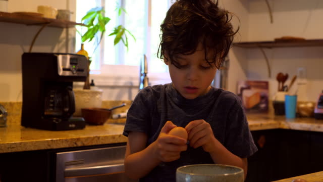 ms young boy trying to crack egg while helping father make breakfast in kitchen - kitchen stock videos & royalty-free footage