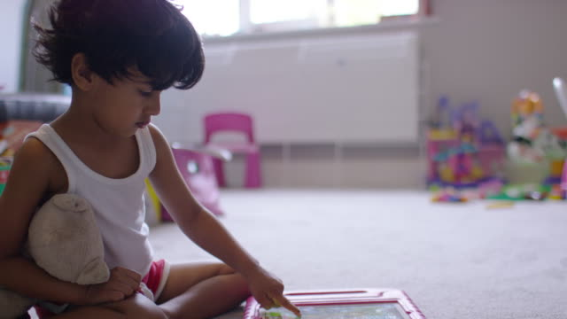 Young boy using a digital tablet game