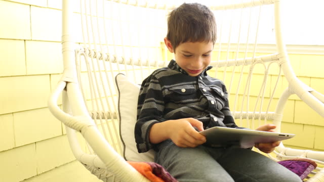 A young boy using a tablet device inside of a colorful home.