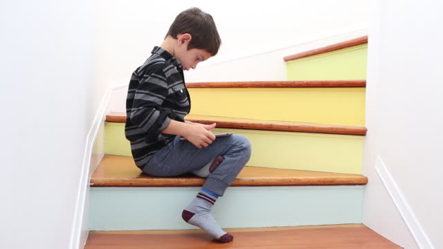 a young boy using a tablet device inside of a colorful home. - nur jungen stock-videos und b-roll-filmmaterial