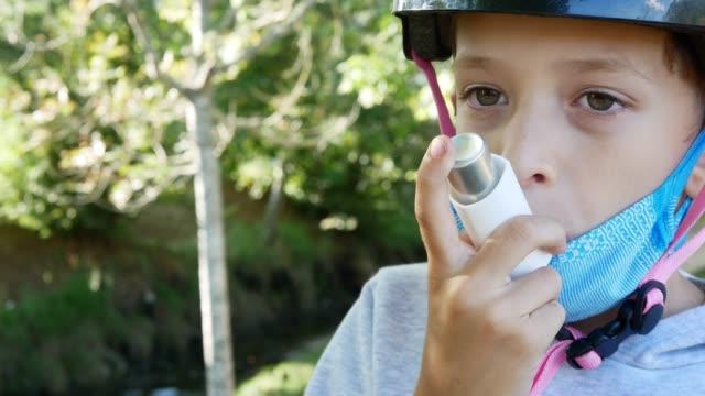vidéos et rushes de young boy using an inhalator outdoors - inhalateur