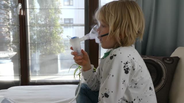 stockvideo's en b-roll-footage met jonge jongen met behulp van astma inhalator. - alleen jongens