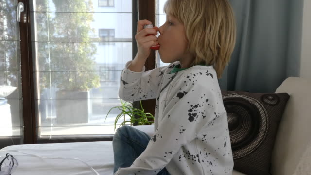 vídeos de stock e filmes b-roll de young boy using asthma inhaler. - inalar
