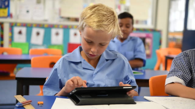 Young boy using digital tablet in school classroom