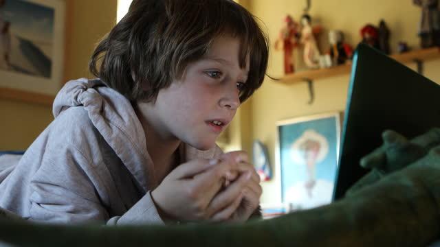 stockvideo's en b-roll-footage met young boy using laptop for video meeting - alleen jongens