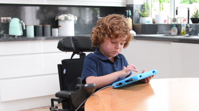 vídeos de stock e filmes b-roll de young boy using tablet in wheelchair at home - acessibilidade