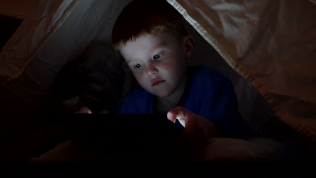 young boy using tech or watching a film on digital tablet in the darkness of a camp - blanket stock videos & royalty-free footage