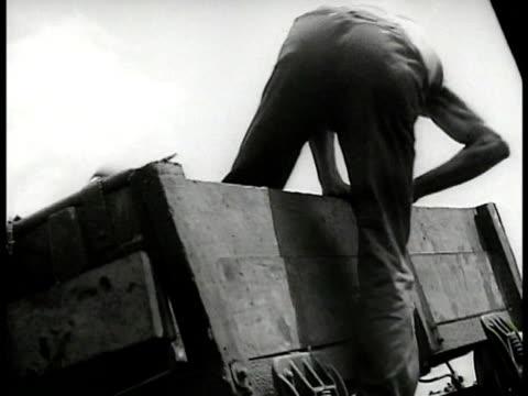 vídeos y material grabado en eventos de stock de young boy w/ man gloves sorting coal. miners shoveling coal from truck into shute. - 1935