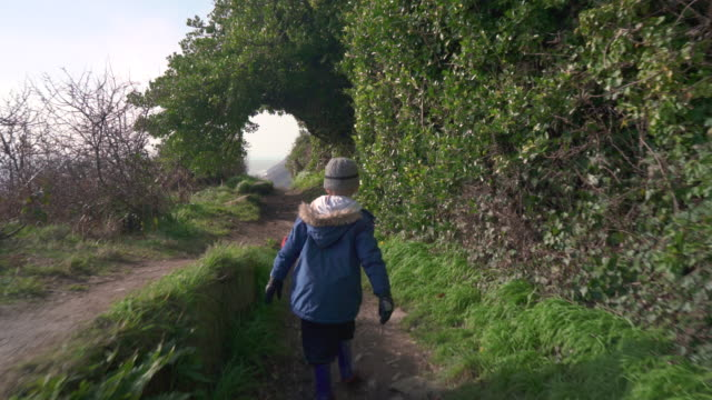 young boy walking along coastal footpath - ein junge in gummistiefel stock-videos und b-roll-filmmaterial