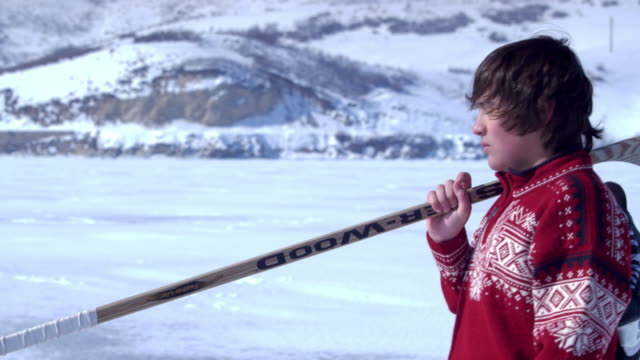 young boy walking through snow with hockey gear. - one teenage boy only stock videos & royalty-free footage