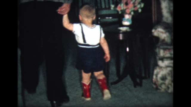 1957 young boy walks in new red boots