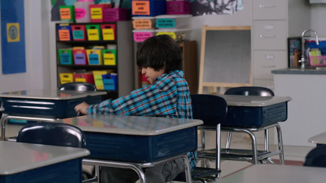 A young boy walks into an empty classroom and begins unpacking at his desk.