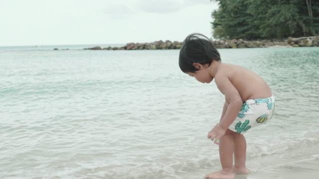stockvideo's en b-roll-footage met jonge jongen loopt uit naar de golven - one baby boy only