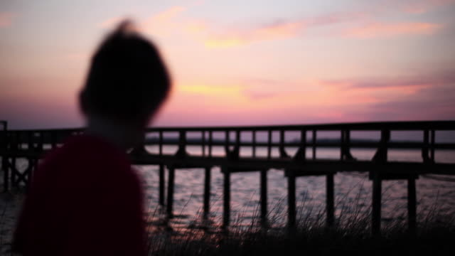 young boy walks toward wooden dock as the sun sets over the water - wilmington north carolina stock-videos und b-roll-filmmaterial