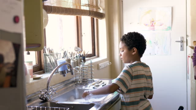 young boy washing dishes with his father at home - chores stock videos & royalty-free footage