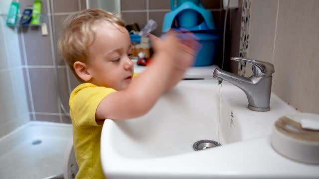 vídeos y material grabado en eventos de stock de jovencito lavándose la cara - agua del grifo