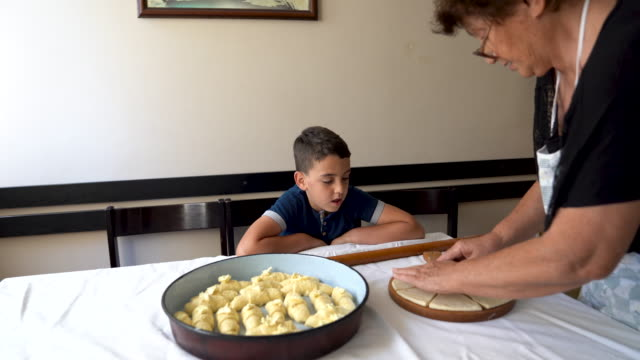 young boy watching his grandmother prepare homemade pastry - french food stock videos & royalty-free footage