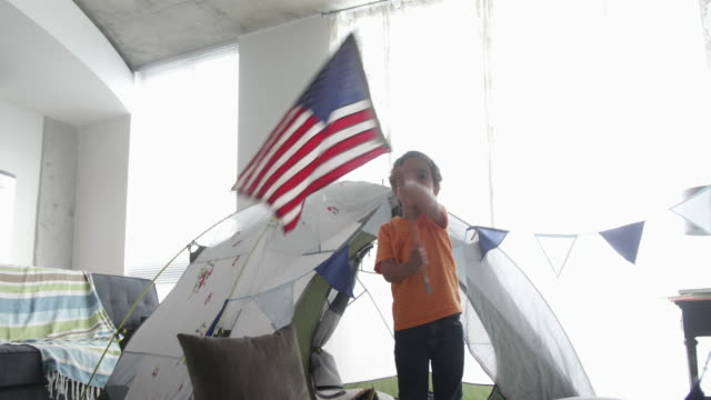 young boy waving flag in front of home made fort, mum sits on sofa reading. - pillow stock videos & royalty-free footage