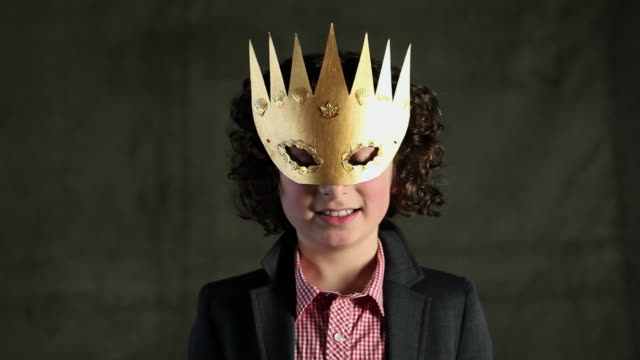 vídeos de stock, filmes e b-roll de young boy wearing gold crown mask - fantasia conceito