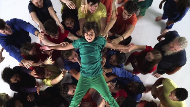 Young Boy Wearing Green Crowdsurfs
